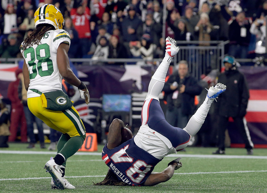 . New England Patriots wide receiver Cordarrelle Patterson (84) lands in the end zone in front of Green Bay Packers cornerback Tramon Williams (38) for a touchdown during the first half of an NFL football game, Sunday, Nov. 4, 2018, in Foxborough, Mass. (AP Photo/Steven Senne)