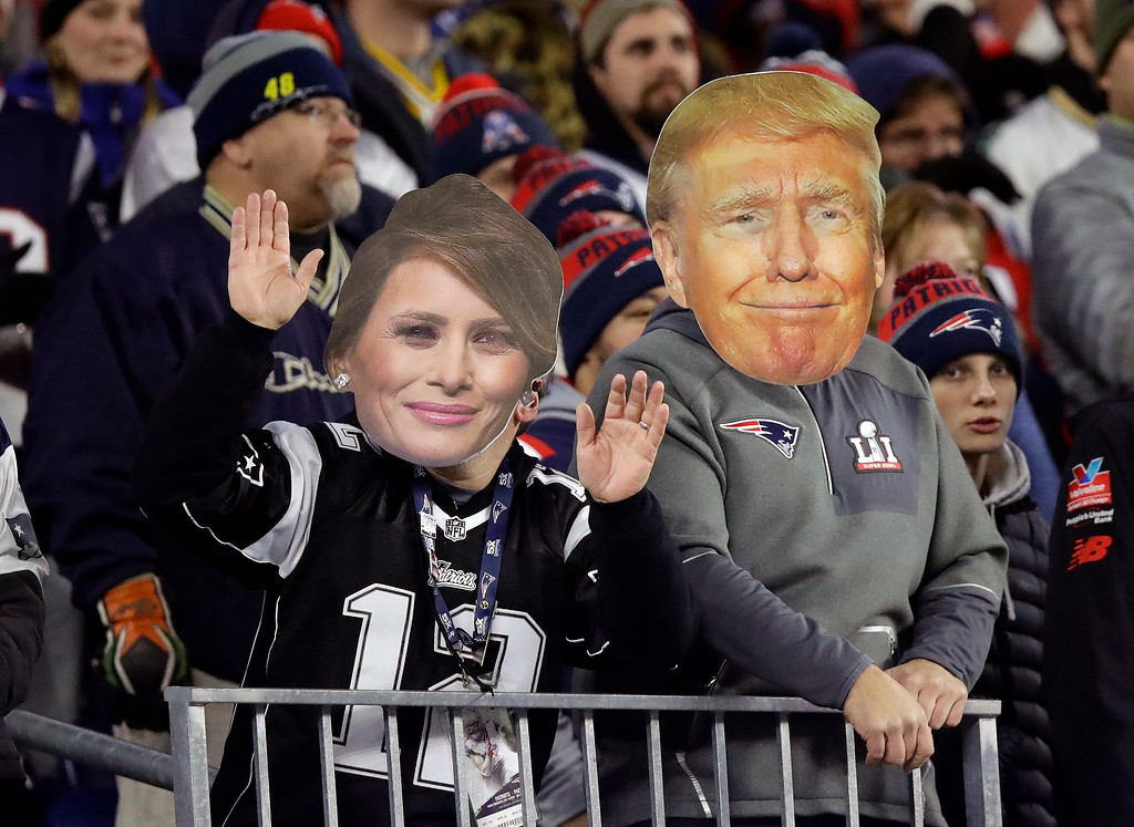 . New England Patriots fans wear large cut-out photos of President Donald Trump, right, and first lady Melania Trump during the second half of an NFL football game between the Patriots and the Green Bay Packers, Sunday, Nov. 4, 2018, in Foxborough, Mass. (AP Photo/Charles Krupa)