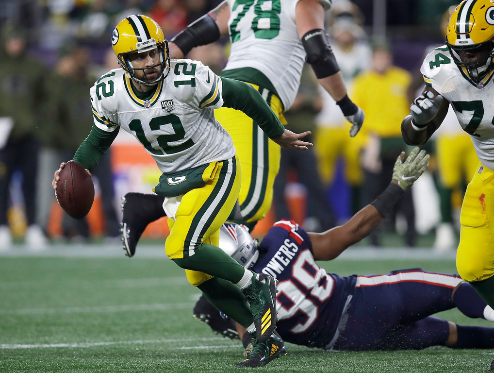 . Green Bay Packers quarterback Aaron Rodgers (12) scrambles away from New England Patriots defensive end Trey Flowers (98) during the first half of an NFL football game, Sunday, Nov. 4, 2018, in Foxborough, Mass. (AP Photo/Charles Krupa)