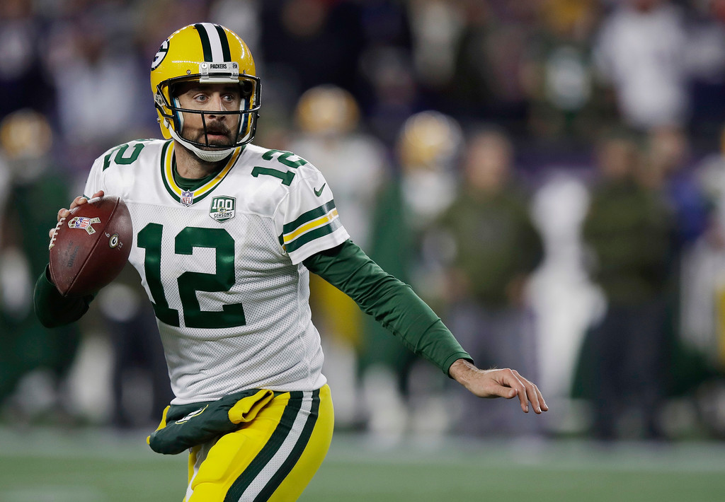 . Green Bay Packers quarterback Aaron Rodgers scrambles against the New England Patriots during the first half of an NFL football game, Sunday, Nov. 4, 2018, in Foxborough, Mass. (AP Photo/Charles Krupa)