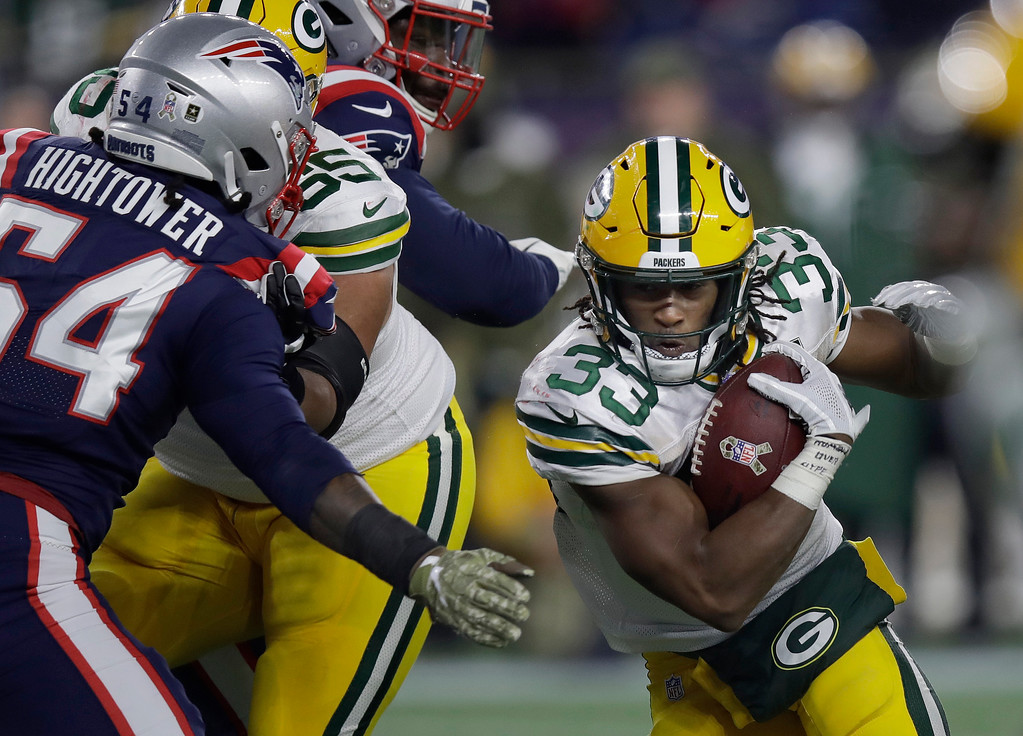 . Green Bay Packers running back Aaron Jones (33) tries to run past New England Patriots linebacker Dont\'a Hightower (54) during the second half of an NFL football game, Sunday, Nov. 4, 2018, in Foxborough, Mass. (AP Photo/Charles Krupa)