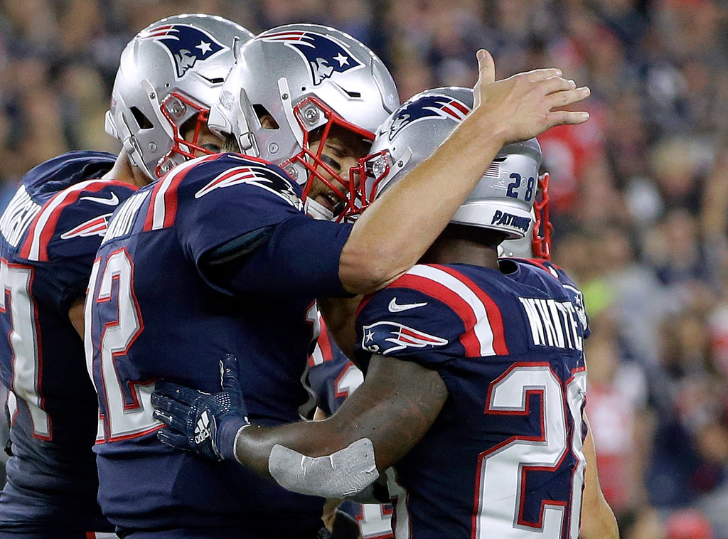 . New England Patriots quarterback Tom Brady, left, congratulates running back James White after his touchdown run against the Indianapolis Colts during the first half of an NFL football game, Thursday, Oct. 4, 2018, in Foxborough, Mass. (AP Photo/Steven Senne)