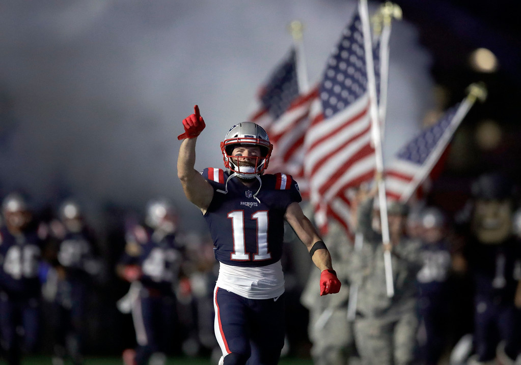 . New England Patriots wide receiver Julian Edelman charges onto the field in front of American flags before an NFL football game against the Indianapolis Colts, Thursday, Oct. 4, 2018, in Foxborough, Mass. (AP Photo/Charles Krupa)