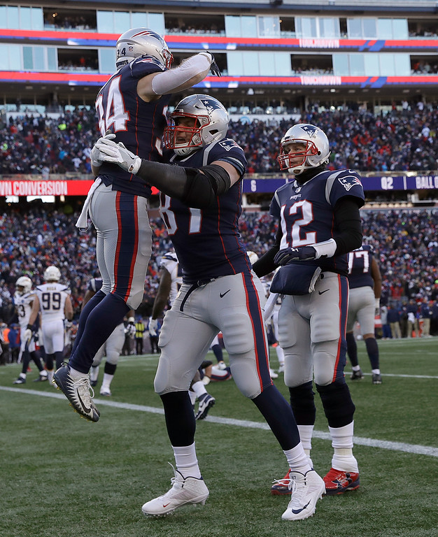 . New England Patriots running back Rex Burkhead (34) gets a lift from Rob Gronkowski, center, as Tom Brady (12) joins the celebration after Burkhead\'s touchdown during the first half of an NFL divisional playoff football game against the Los Angeles Chargers, Sunday, Jan. 13, 2019, in Foxborough, Mass. (AP Photo/Charles Krupa)