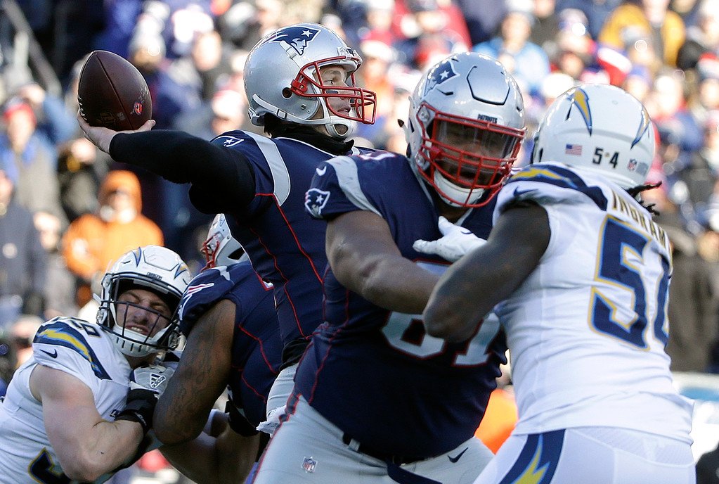 . New England Patriots quarterback Tom Brady, center, passes under pressure from Los Angeles Chargers defensive end Melvin Ingram (54) during the first half of an NFL divisional playoff football game, Sunday, Jan. 13, 2019, in Foxborough, Mass. (AP Photo/Steven Senne)