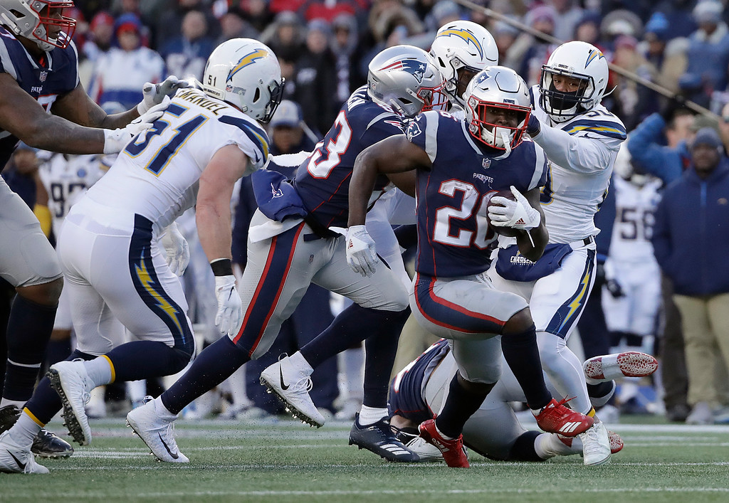 . New England Patriots running back Sony Michel (26) runs from Los Angeles Chargers outside linebacker Kyle Emanuel (51) during the second half of an NFL divisional playoff football game, Sunday, Jan. 13, 2019, in Foxborough, Mass. (AP Photo/Elise Amendola)