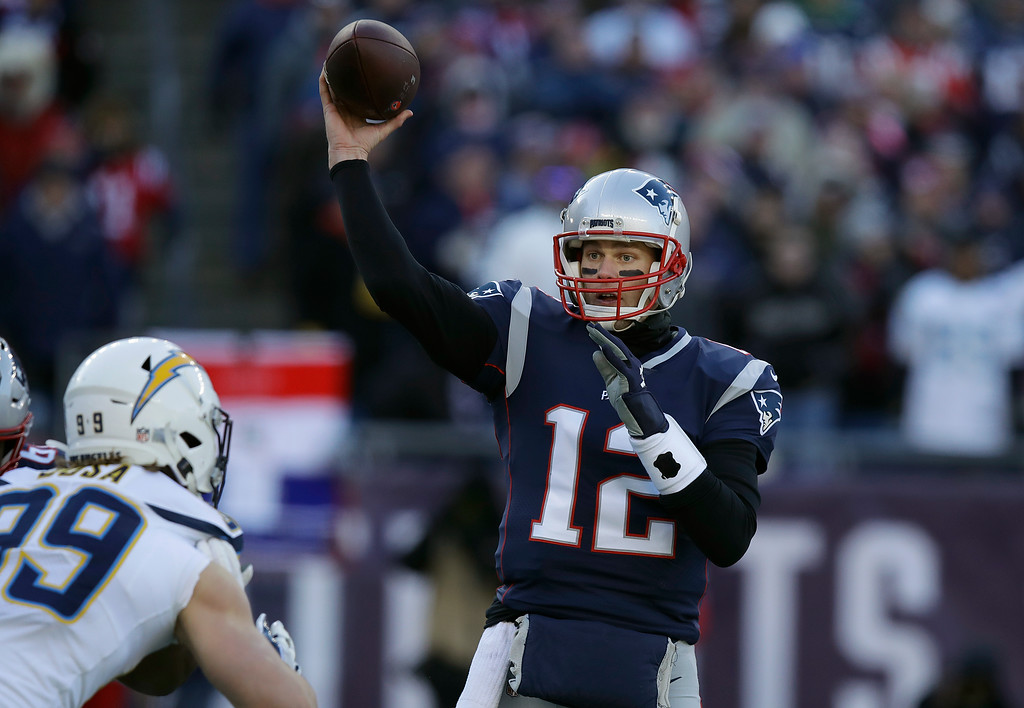 . New England Patriots quarterback Tom Brady (12) passes under pressure from Los Angeles Chargers defensive end Joey Bosa (99) during the first half of an NFL divisional playoff football game, Sunday, Jan. 13, 2019, in Foxborough, Mass. (AP Photo/Charles Krupa)