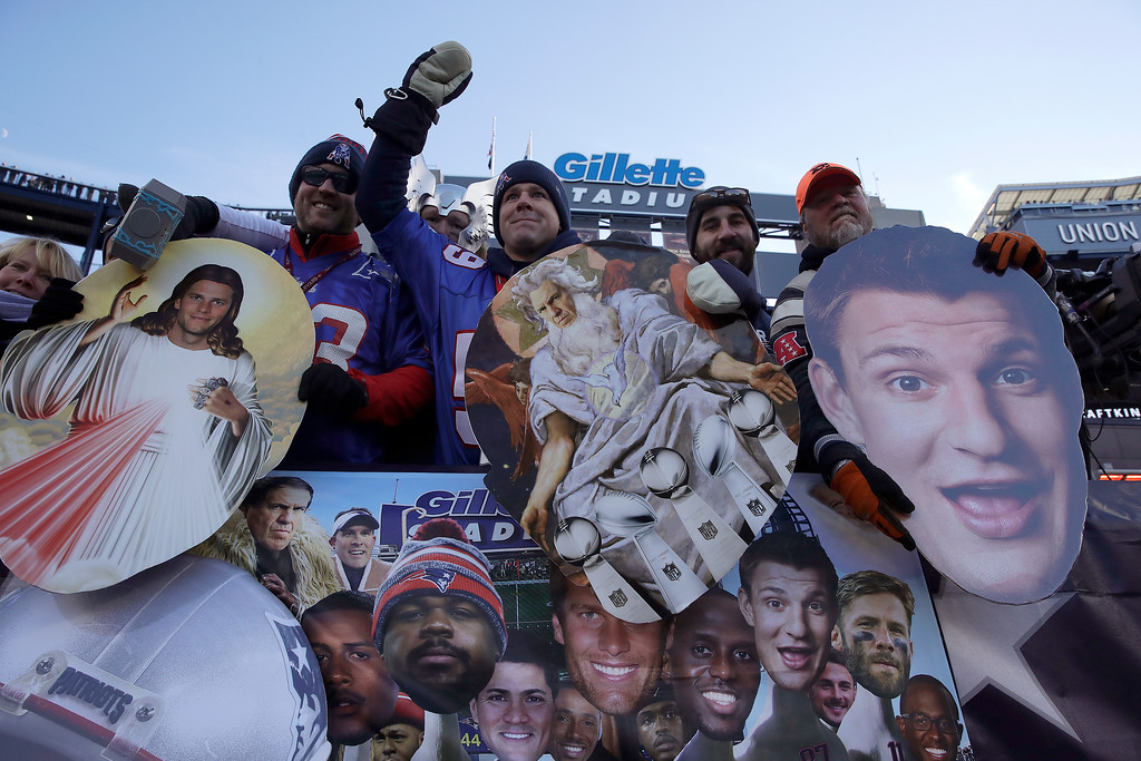 . New England Patriots fans hold photos of members of the Patriots team during the first half of an NFL divisional playoff football game between the Los Angeles Chargers and the Patriots, Sunday, Jan. 13, 2019, in Foxborough, Mass. (AP Photo/Charles Krupa)