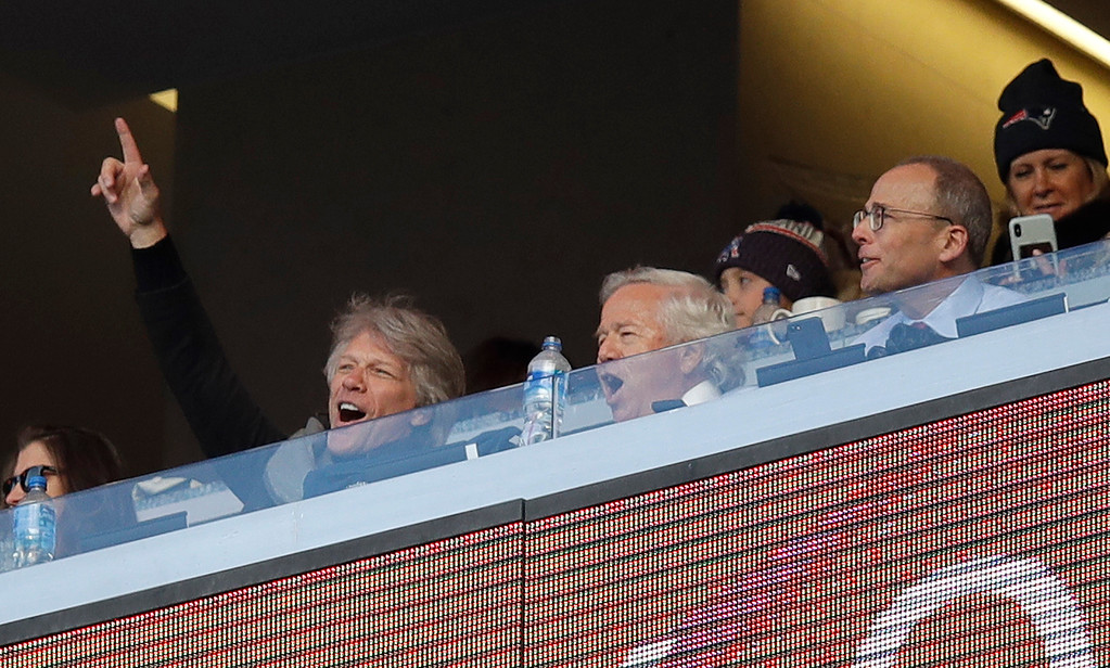 . Singer Jon Bon Jovi, left, cheers while sitting in the box of New England Patriots owner Robert Kraft, center, and president Jonathan Kraft, right, during the second half of an NFL divisional playoff football game between the Los Angeles Chargers and the Patriots, Sunday, Jan. 13, 2019, in Foxborough, Mass. (AP Photo/Charles Krupa)