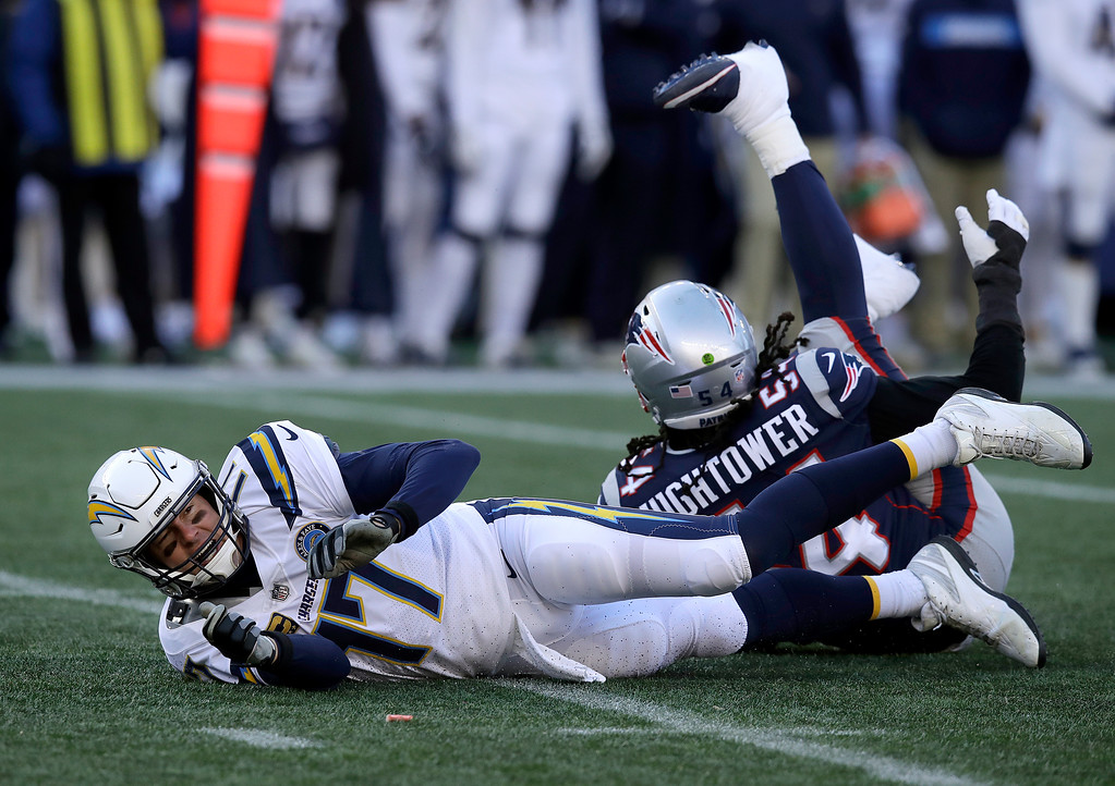 . Los Angeles Chargers quarterback Philip Rivers (17) hits the turf after being knocked down by New England Patriots linebacker Dont\'a Hightower (54) during the first half of an NFL divisional playoff football game, Sunday, Jan. 13, 2019, in Foxborough, Mass. (AP Photo/Charles Krupa)