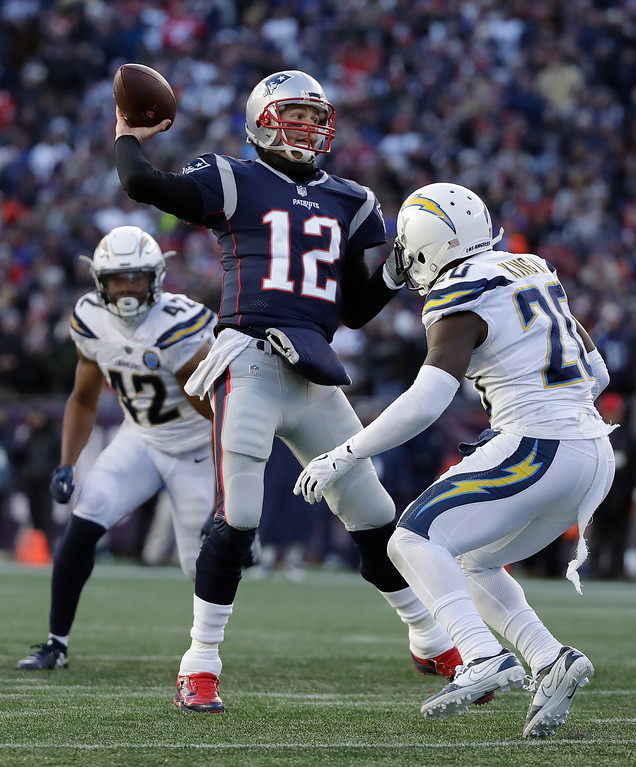 . New England Patriots quarterback Tom Brady passes between Los Angeles Chargers linebacker Uchenna Nwosu (42) and defensive back Desmond King (20) during the second half of an NFL divisional playoff football game, Sunday, Jan. 13, 2019, in Foxborough, Mass. (AP Photo/Elise Amendola)