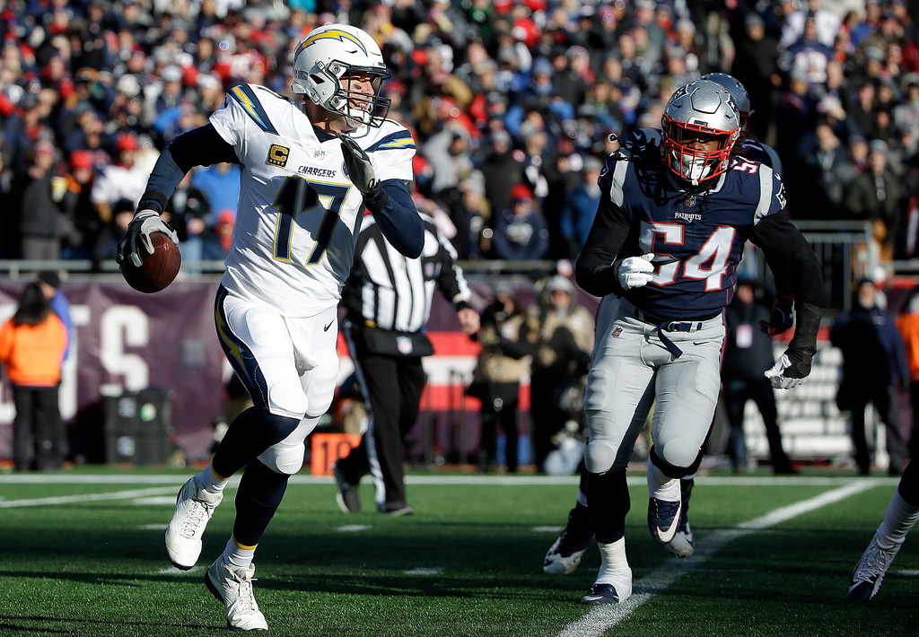 . Los Angeles Chargers quarterback Philip Rivers (17) scrambles away from New England Patriots linebacker Dont\'a Hightower (54) during the first half of an NFL divisional playoff football game, Sunday, Jan. 13, 2019, in Foxborough, Mass. (AP Photo/Steven Senne)