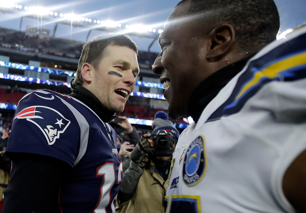 . New England Patriots quarterback Tom Brady, left, and Los Angeles Chargers tight end Antonio Gates speak at midfield after an NFL divisional playoff football game, Sunday, Jan. 13, 2019, in Foxborough, Mass. (AP Photo/Charles Krupa)