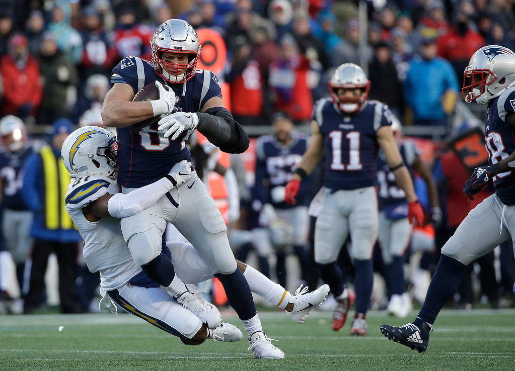 . New England Patriots tight end Rob Gronkowski is tackled by Los Angeles Chargers defensive back Adrian Phillips after catching a pass during the second half of an NFL divisional playoff football game, Sunday, Jan. 13, 2019, in Foxborough, Mass. (AP Photo/Steven Senne)