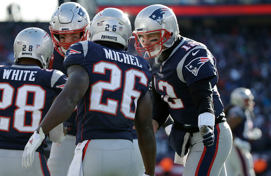 . New England Patriots quarterback Tom Brady, right, celebrates a touchdown run by running back Sony Michel (26) during the first half of an NFL divisional playoff football game against the Los Angeles Chargers, Sunday, Jan. 13, 2019, in Foxborough, Mass. (AP Photo/Elise Amendola)