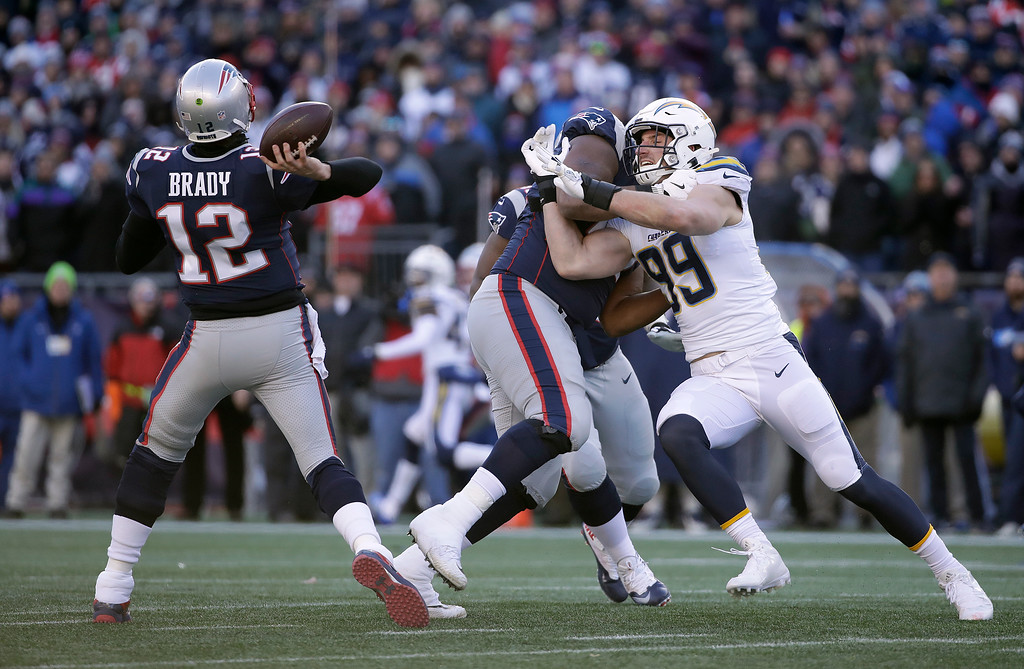 . New England Patriots quarterback Tom Brady (12) passes while tackle Marcus Cannon blocks Los Angeles Chargers defensive end Joey Bosa (99) during the first half of an NFL divisional playoff football game, Sunday, Jan. 13, 2019, in Foxborough, Mass. (AP Photo/Elise Amendola)