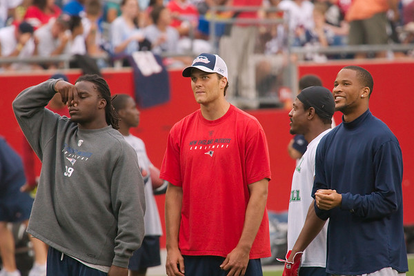 "Laurence Maroney, Tom Brady, Troy Brown, and Jabbar Gaffney watch as Patriots players' ""head shot"" photos are displayed on the jumbotron atop the end zone at the lighthouse end of Gillette Stadium prior to the start of training camp evening session on Mon., Aug. 6, 2007. Mr. Maroney is reacting to the display of Tom Brady's photo on the jumbotron."