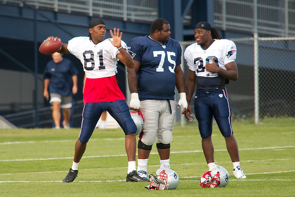 Randy Moss, #81; Vince Wilfork, #75; Laurence Maroney, #39; with head coach Bill Belichick in the distance.