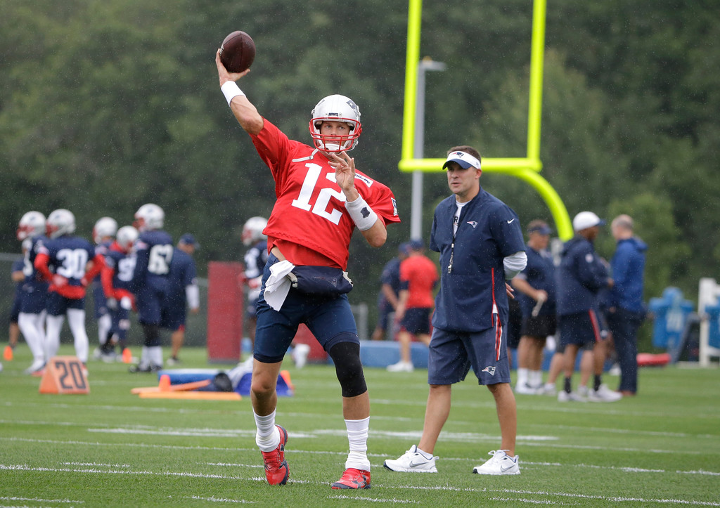 . New England Patriots quarterback Tom Brady (12) passes the ball as offensive coordinator Josh McDaniels, right, looks on during NFL football practice, Thursday, July 26, 2018, in Foxborough, Mass. (AP Photo/Steven Senne)