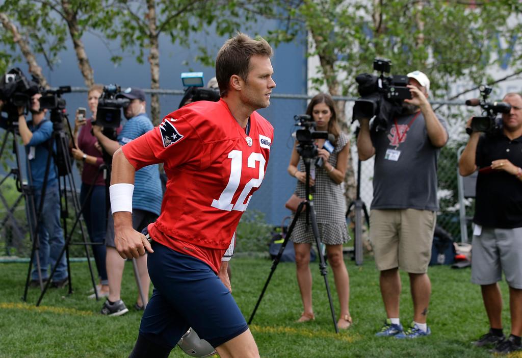 . New England Patriots quarterback Tom Brady (12) runs past members of the media before an NFL football practice, Thursday, July 26, 2018, in Foxborough, Mass. (AP Photo/Steven Senne)
