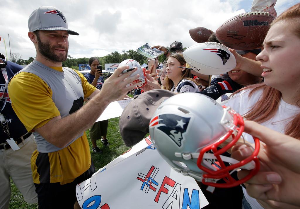 . New England Patriots wide receiver Julian Edelman, left, signs autographs for fans following an NFL football practice, Thursday, July 26, 2018, in Foxborough, Mass. (AP Photo/Steven Senne)