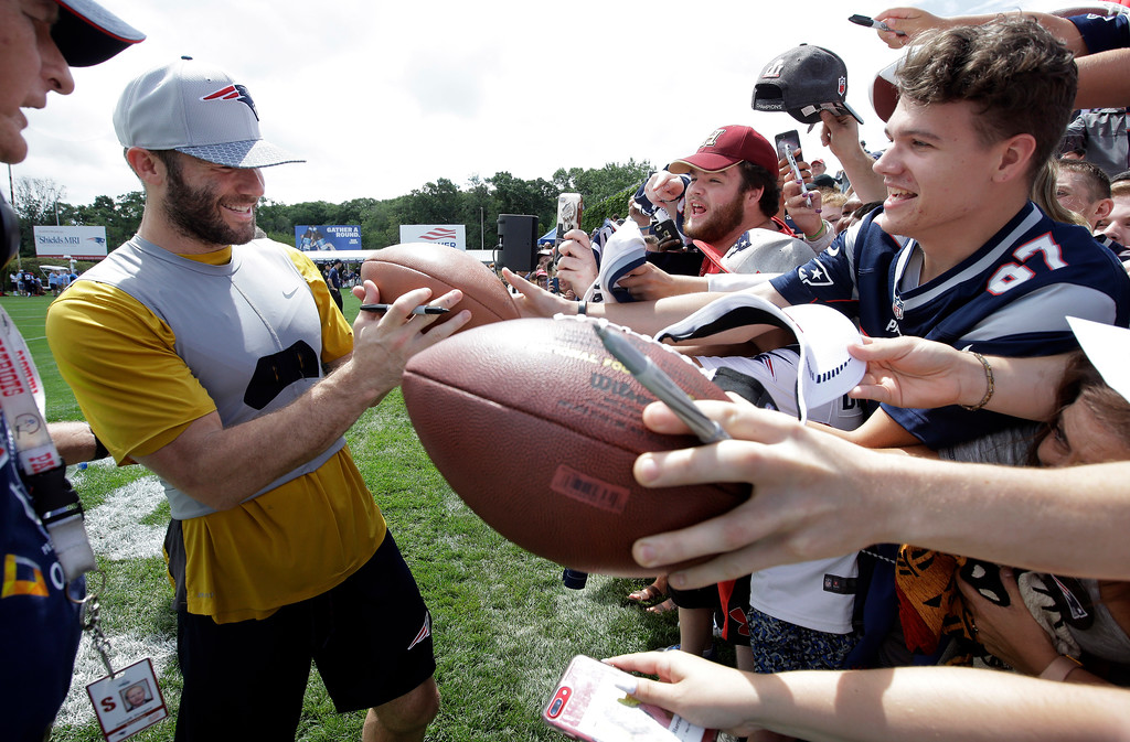 . New England Patriots wide receiver Julian Edelman, center left, signs autographs for fans following an NFL football practice, Thursday, July 26, 2018, in Foxborough, Mass. (AP Photo/Steven Senne)