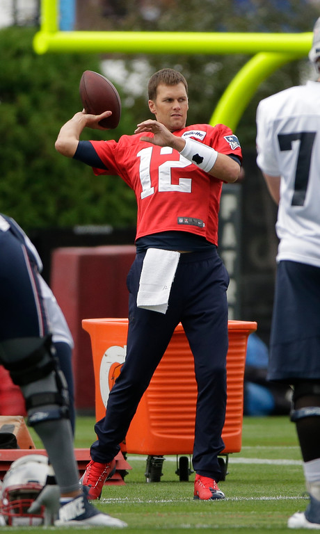 . New England Patriots quarterback Tom Brady (12) throws the ball while warming up on the field at NFL football training camp, Thursday, July 27, 2017, in Foxborough, Mass. (AP Photo/Steven Senne)