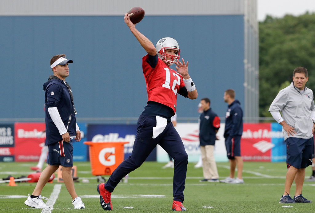 . New England Patriots quarterback Tom Brady (12) winds up for a pass as offensive coordinator Josh McDaniels, left, looks on during NFL football training camp, Thursday, July 27, 2017, in Foxborough, Mass. (AP Photo/Steven Senne)