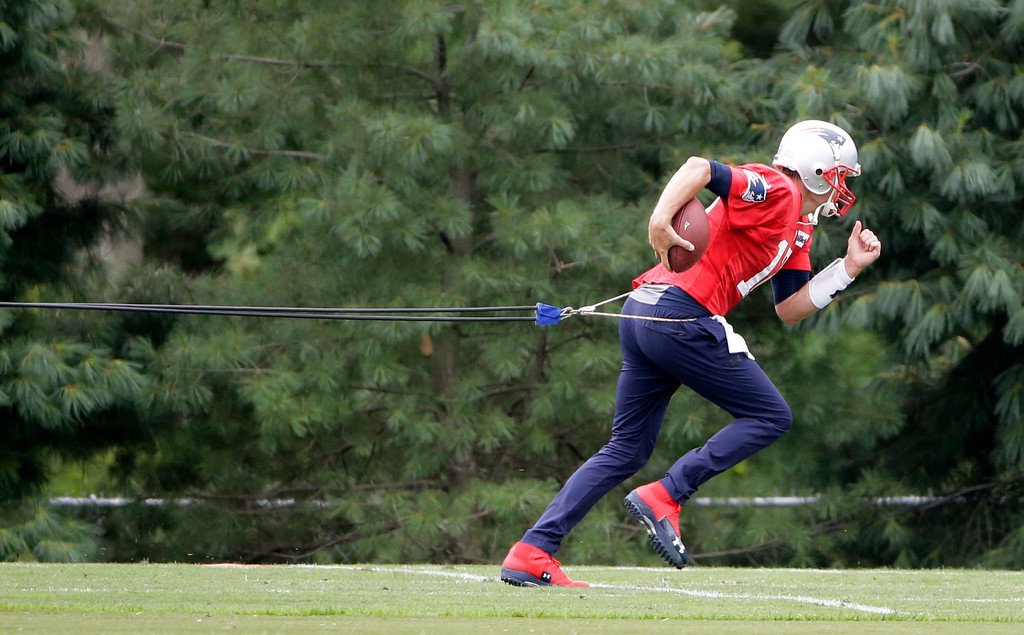 . New England Patriots quarterback Tom Brady works out with a resistance band at NFL football training camp, Thursday, July 27, 2017, in Foxborough, Mass. (AP Photo/Steven Senne)