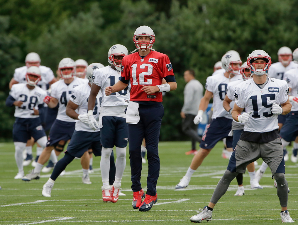 . New England Patriots quarterback Tom Brady (12) warms up at NFL football training camp, Thursday, July 27, 2017, in Foxborough, Mass. (AP Photo/Steven Senne)