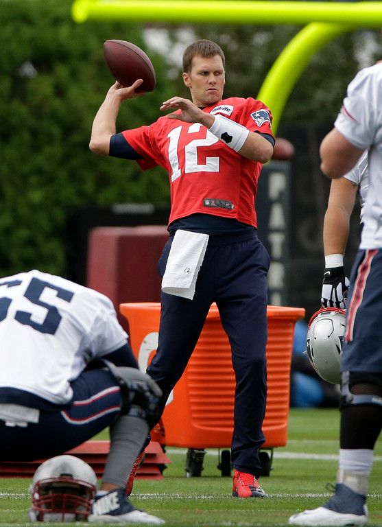 . New England Patriots quarterback Tom Brady (12) winds up to throw the ball during NFL football training camp, Thursday, July 27, 2017, in Foxborough, Mass. (AP Photo/Steven Senne)