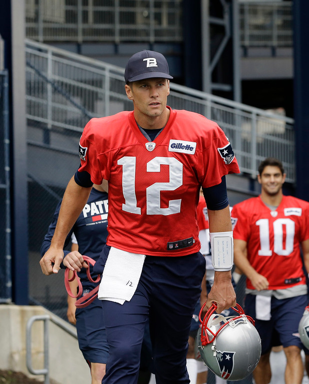 . New England Patriots quarterback Tom Brady (12) and quarterback Jimmy Garoppolo (10) step on the field at NFL football training camp, Thursday, July 27, 2017, in Foxborough, Mass. (AP Photo/Steven Senne)