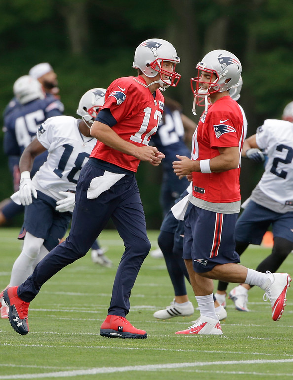 . New England Patriots quarterbacks Tom Brady, center left, and Jimmy Garoppolo, center right, warm up at NFL football training camp, Thursday, July 27, 2017, in Foxborough, Mass. (AP Photo/Steven Senne)