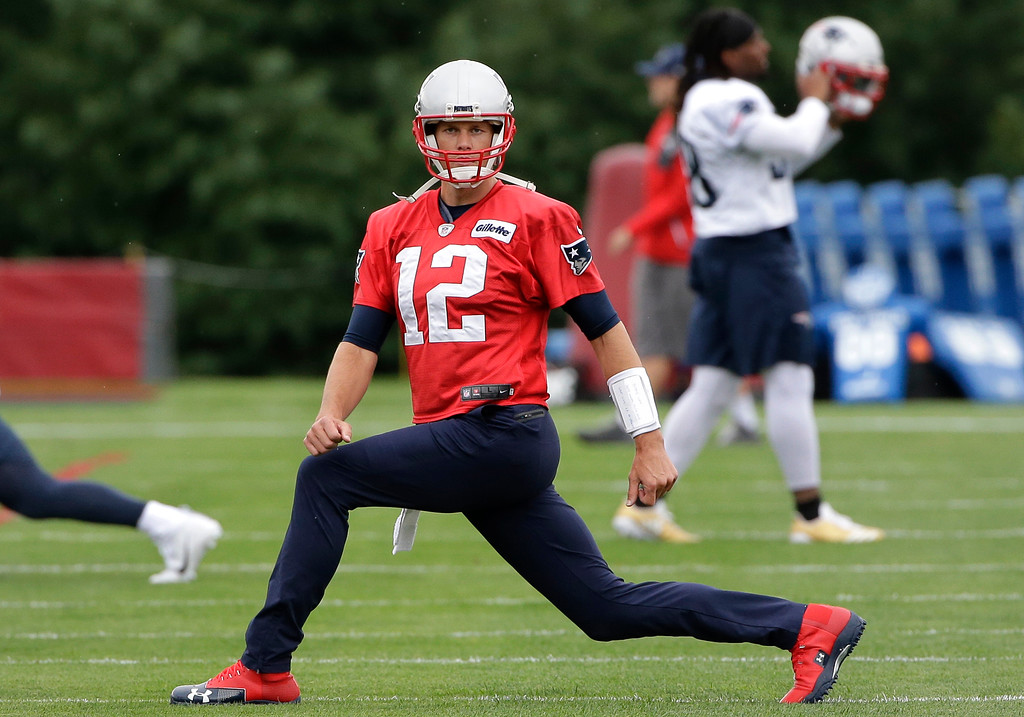 . New England Patriots quarterback Tom Brady (12) stretches while warming up at NFL football training camp, Thursday, July 27, 2017, in Foxborough, Mass. (AP Photo/Steven Senne)