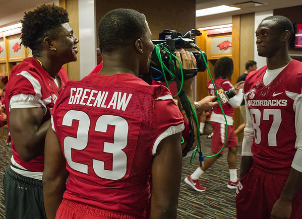 La'Michael Pettway (left) and Dre Greenlaw (center) distract Dominique Reed (87) as he is interviewed by media at the Razorback Media Day on Sunday, August 9, 2015 at the Fred W. Smith Football Center in Fayetteville, Arkansas.   (Alan Jamison, Nate Allen Sports Service).