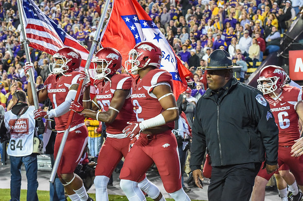 Arkansas Razorbacks wide receiver Jared Cornelius (1) and Arkansas Razorbacks wide receiver Dominique Reed (87) carry the flags onto the field along with Arkansas Razorbacks defensive back D.J. Dean (2) just prior to the start of a football game between Arkansas and LSU on November 14, 2015.    (Alan Jamison, Nate Allen Sports Service)