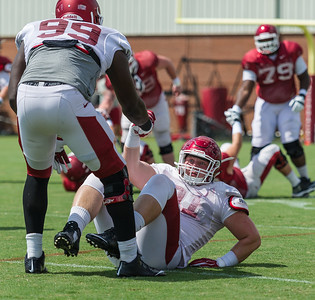 Brandon Lewis (99) helps Hjalte Froholdt (91) up from the ground during warm-ups at the Razorback Football practice on Tuesday, August 11, 2015 at the Fred W. Smith Football Center in Fayetteville, Arkansas.   (Alan Jamison, Nate Allen Sports Service).