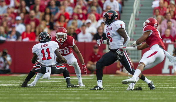 Arkansas safety Rohan Gaines (26) prepares to tackle Texas Tech wide receiver Jakeem Grant (11) during a football game between the Arkansas Razorbacks and the Texas Tech Red Raiders at Reynolds Razorback Stadium at the University of Arkansas in Fayetteville, Arkansas.   Texas Tech won 35-24.  (Alan Jamison, Nate Allen Sports Service)
