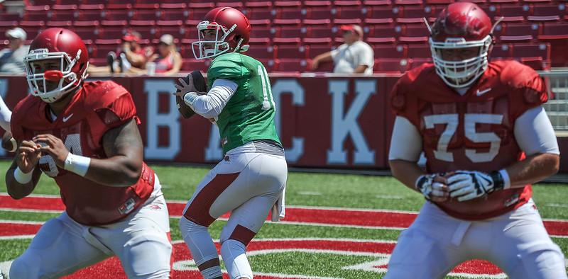 Brandon drops back behind the protection of Reeve Koehler and Zach Rogers at the Razorback Football practice on Saturday, August 15, 2015 at Reynolds Razorback Stadium in Fayetteville, Arkansas.   (Alan Jamison, Nate Allen Sports Service).