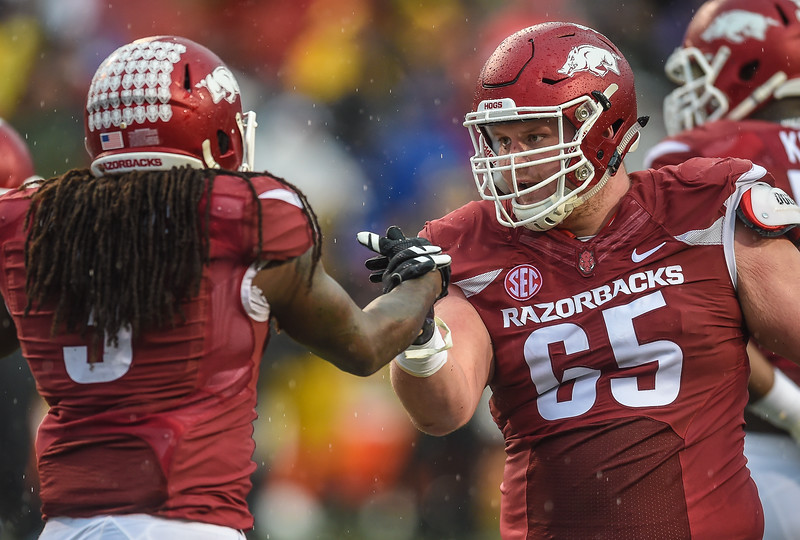Arkansas Razorbacks offensive lineman Mitch Smothers (65) congratulates Arkansas Razorbacks running back Alex Collins (3) after Collins' rushing touchdown during a football game between Arkansas and Missouri on November 27, 2015.    (Alan Jamison, Nate Allen Sports Service)