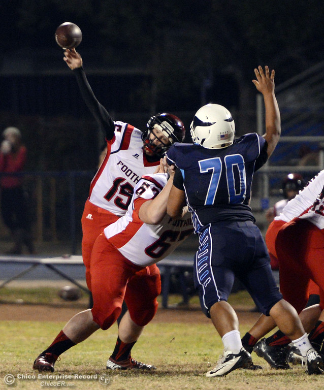 . Pleasant Valley High\'s #70 Josh Alvarez (right) defends against Foothill High\'s #15 Ryan Pollard (left) who throws a pass in the second quarter of their football game at PVHS Asgard Yard Friday, October 11, 2013 in Chico, Calif.  (Jason Halley/Chico Enterprise-Record)