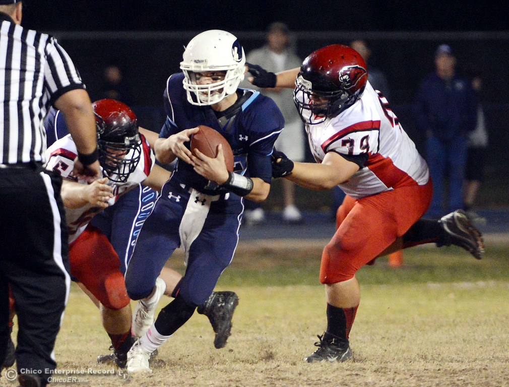 . Pleasant Valley High\'s #12 Trent Darms (left) is tackled against Foothill High\'s #58 Kory Silva (left)  and #79 Wyatt Landreth (right) in the second quarter of their football game at PVHS Asgard Yard Friday, October 11, 2013 in Chico, Calif.  (Jason Halley/Chico Enterprise-Record)