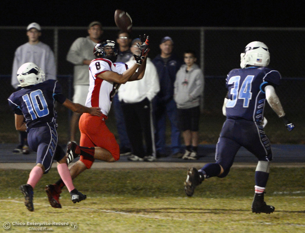 . Pleasant Valley High\'s #10 Tucker LaRue (left) and #34 Cale Crawford (right) watch  Foothill High\'s #8 Andrew Horn (center) complete a catch for a touchdown in the second quarter of their football game at PVHS Asgard Yard Friday, October 11, 2013 in Chico, Calif.  (Jason Halley/Chico Enterprise-Record)