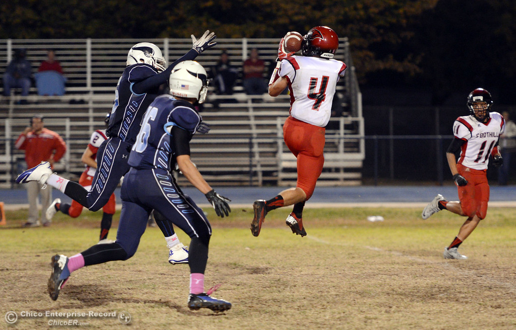 . Foothill High\'s #4 Luke Kelly (center) leaps up for an interception against Pleasant Valley High in the third quarter of their football game at PVHS Asgard Yard Friday, October 11, 2013 in Chico, Calif.  (Jason Halley/Chico Enterprise-Record)