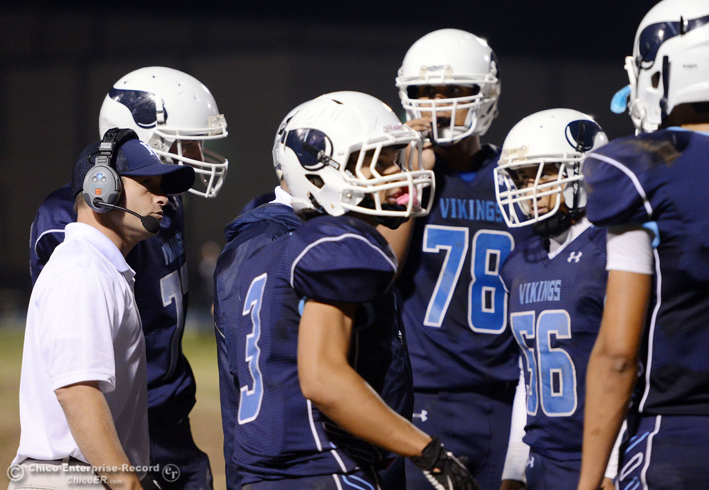 . Pleasant Valley High head coach Mark Cooley (left) talks to the team during a timeout against Foothill High in the second quarter of their football game at PVHS Asgard Yard Friday, October 11, 2013 in Chico, Calif.  (Jason Halley/Chico Enterprise-Record)