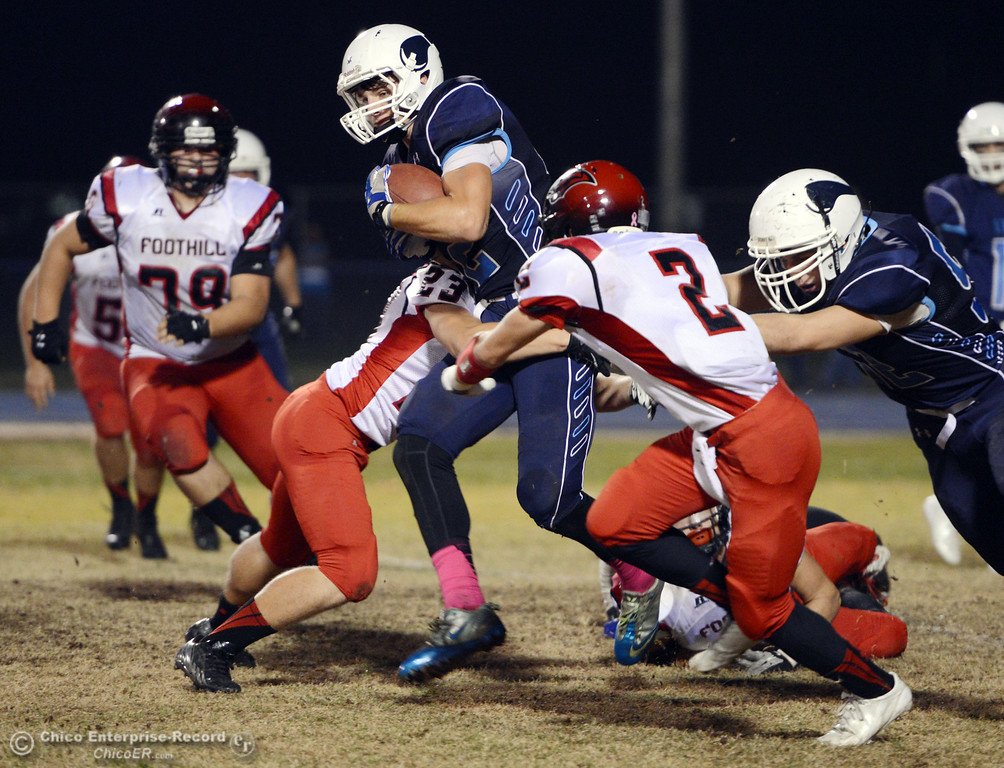 . Pleasant Valley High\'s #42 Chad Olsen (center) is tackled against Foothill High\'s #23 Zac Thompson (left) and #2 Chandler Roe (right) in the second quarter of their football game at PVHS Asgard Yard Friday, October 11, 2013 in Chico, Calif.  (Jason Halley/Chico Enterprise-Record)