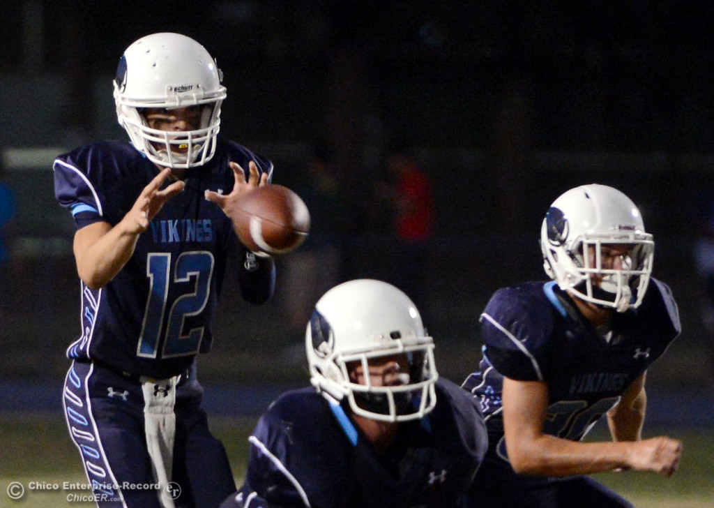 . Pleasant Valley High\'s #12 Trent Darms takes a snap against Lassen High in the first quarter of their football game at PVHS Asgard Yard Friday, September 6, 2013 in Chico, Calif. (Jason Halley/Chico Enterprise-Record)
