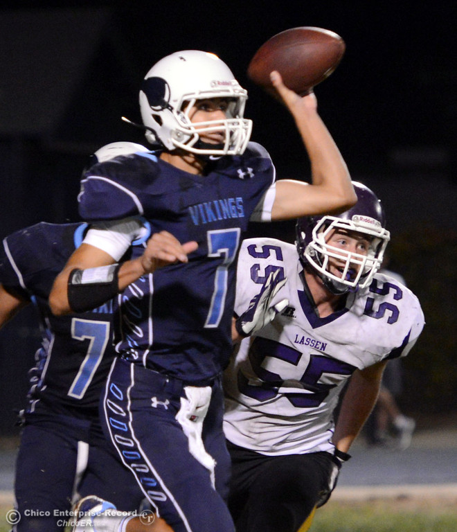 . Pleasant Valley High\'s #7 Zane Ferguson (left) passes against Lassen High\'s #55 Colton Faure (right) in the fourth quarter of their football game at PVHS Asgard Yard Friday, September 6, 2013 in Chico, Calif. (Jason Halley/Chico Enterprise-Record)