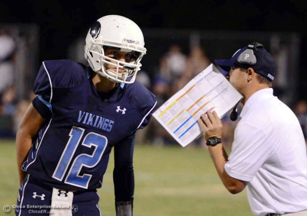 . Pleasant Valley High\'s #12 Trent Darms (left) gets the play from coach Mark Cooley (right) against Lassen High in the second quarter of their football game at PVHS Asgard Yard Friday, September 6, 2013 in Chico, Calif. (Jason Halley/Chico Enterprise-Record)