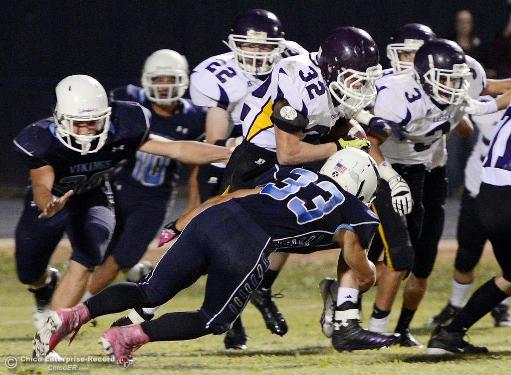 . Pleasant Valley High\'s #33 Taylor Wright (bottom) tackles against Lassen High\'s #32 Skyler Ingwerson (top) in the third quarter of their football game at PVHS Asgard Yard Friday, September 6, 2013 in Chico, Calif. (Jason Halley/Chico Enterprise-Record)